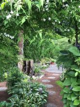 A narrow pathway through a shady Mill Creek garden with a water feature. Photo courtesy of Mill Creek Garden Club.