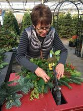 Kathy Hamilton carefully places the next bundle of greens in the machine. Photo courtesy of Mill Creek Garden Club.
