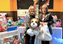 Sandy Somers and Julie Jacobson artistically arrange the toys donated by MCGC Members. Photo courtesy of Mill Creek Garden Club.