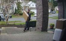 Thief bringing empty package to front porch. Blue SUV can be seen in background. Photo courtesy of Mill Creek Police.
