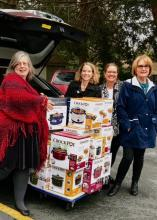 Mill Creek Women's Club members delivering crockpots for clients at YWCA Pathways for Women. From left to right are Nora Karena (YWCA), Vicki Von Stubbe (YWCA), Julie Bronemann (MCWC Philanthropy Chair), and Nancy Knox (MCWC President). Photo courtesy of YWCA.
