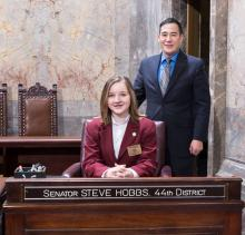 Viola Cipriano with Senator Steve Hobbs at his Washington State Senate desk. Photo courtesy of Washington State Senate.